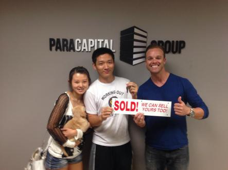 Tyler holding a sold sign with 2 clients