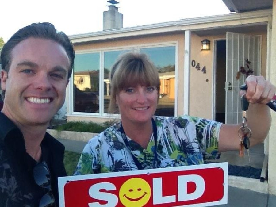 Tyler holding sold sign with client in front of house